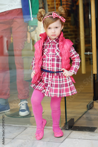Little cute girl in pink dress poses showcase of clothing store