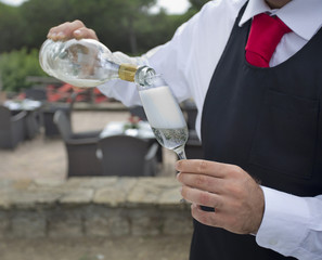waiter pouring a glass of  wine or champagne outside