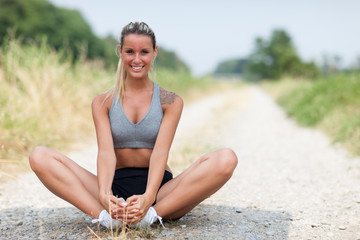 Smiling blonde woman is stretching on a field street