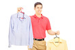 Smiling male holding two hangers with shirts