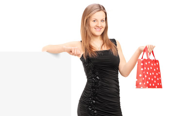 Young female with a gift bag standing next to a blank panel