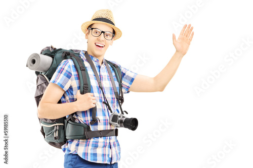 Male tourist with backpack waving with his hand