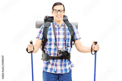 Smiling hiker with backpack and hiking poles posing