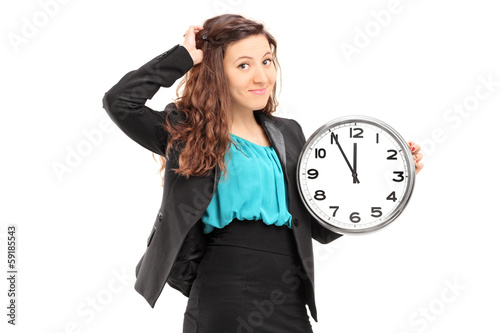 Young smiling businesswoman holding a wall clock