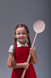 Young girl with  large wooden spoon