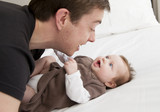 Fototapety Young father playing with sweet baby girl