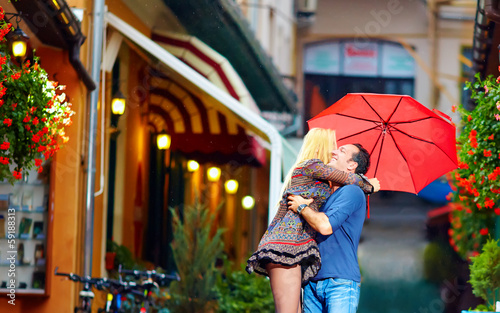 happy couple in love embracing on colorful street