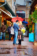 couple in love standing under the rain on colorful street