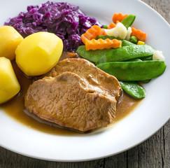 Schweinebraten mit kartoffeln, Gemüse und Rotkohl