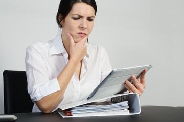 Verwirrte Frau brütet über einem Problem mit einem Tablet