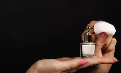 female hand with perfume bottle
