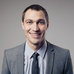 Pleasant businessman portrait on grey background
