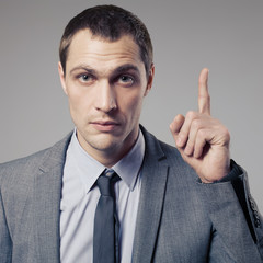 Young businessman call for attention on gray background