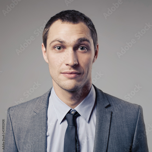 Pleasant businessman portrait on grey background