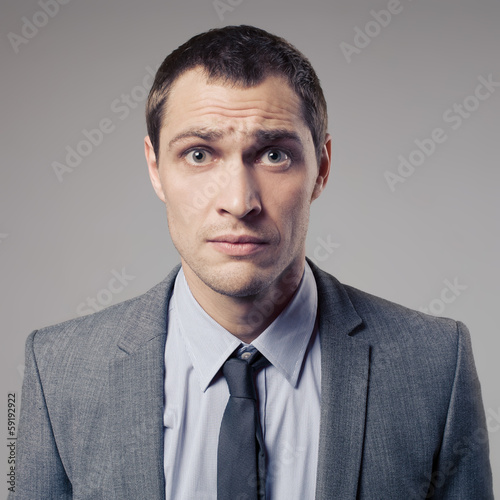 Confused Businessman On Gray Background