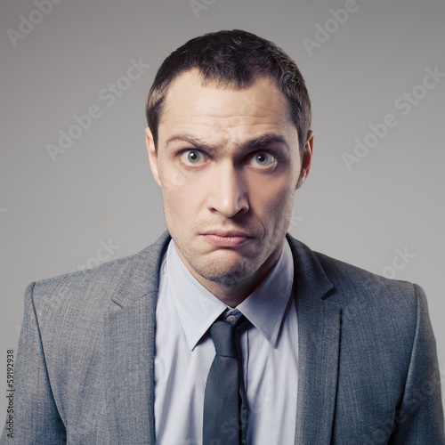 Angry Businessman On Gray Background