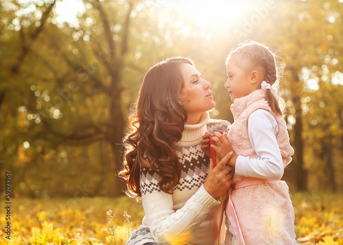 Mom and daughter having fun in autumn park.