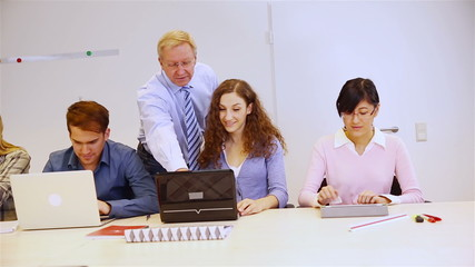 Teacher helping students with computers