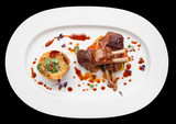 Grilled rack of lamb in oval plate isolated on black