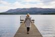 lonely woman walking on a pier
