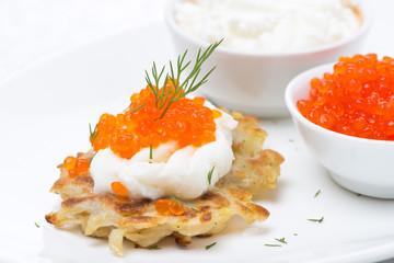 potato pancakes with red caviar and sour cream, close-up