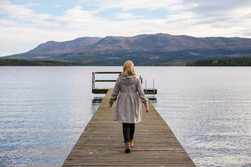 lonely woman walking on a pier