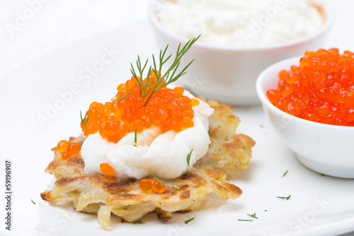 potato pancakes with red caviar and sour cream, close-up