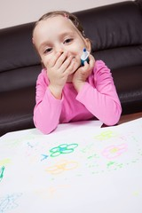 Adorable little girl amused by her drawing