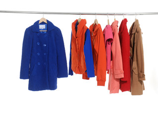 Variety of female coat and clothing hanging on hangers