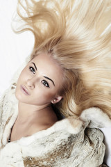 Beautiful blond woman in mink fur on the floor. long hair