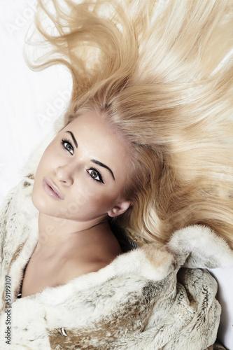 Beautiful blond woman in mink fur on the floor. long hair