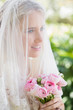 Happy bride wearing veil over face holding rose bouquet