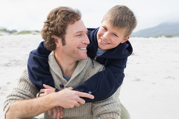 Man piggybacking his cheerful son at beach