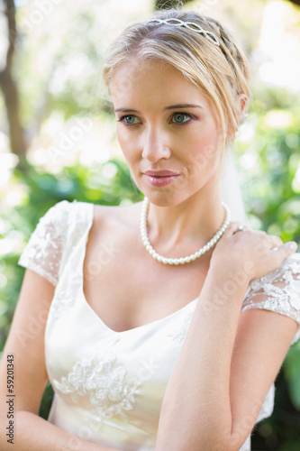 Smiling blonde bride in pearl necklace
