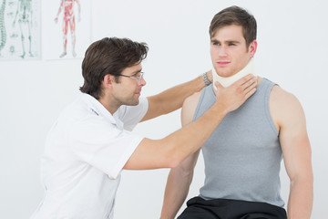 Male doctor examining a patients neck