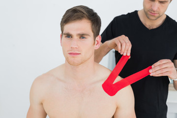 Physiotherapist putting red kinesio tape on patients shoulder