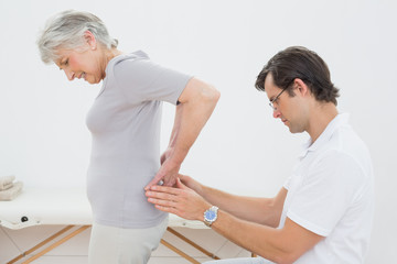 Physiotherapist examining senior woman's back