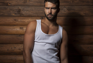 Portrait of beautiful fashionable man against wooden wall.