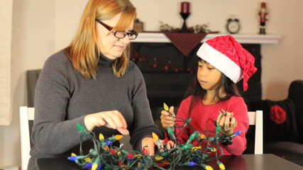 Mother And Daughter Untangling Christmas Lights