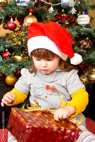 Happy child in Santa hat opening Christmas gift box