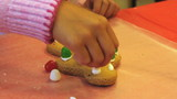 Putting Gum Drops On Christmas Gingerbread Man Cookie
