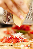 Cook's hands grating parmesan over tomato bruschettas