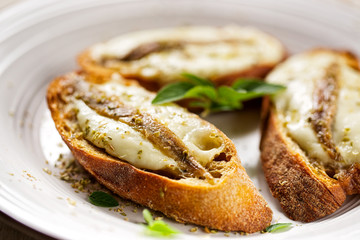 Crostini with fish, mozzarella and oregano