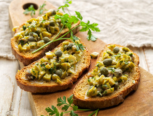 Bruschetta with green olives, anchovies, capers and parsley