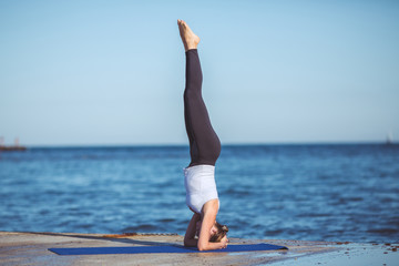 Young beautiful woman on the beach making yoga