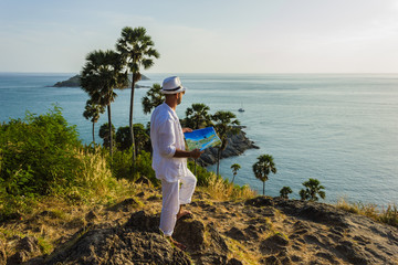 The man  in a white suit and hat sitting on a rock on the sea ba