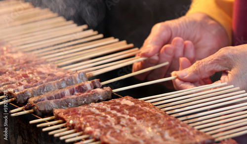 hand while turning the skewers of cooked meat