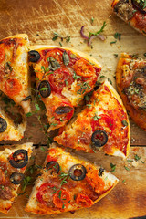 Homemade pizza with tomato, black olives and herbs