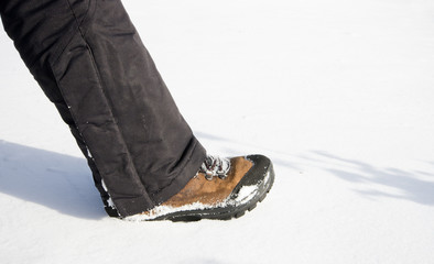 Female leg makes step in winter pants and shoes on snow