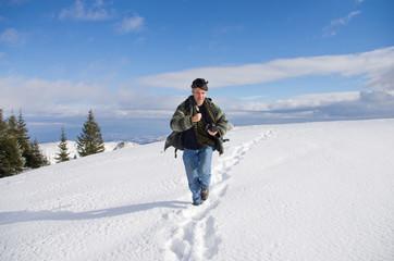 Man running on snowy hill on sunny day